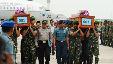 Indonesian soldiers carry coffins containing victims of the AirAsia flight QZ8501 crash at the Indonesian Air Force Military Base in Surabaya.