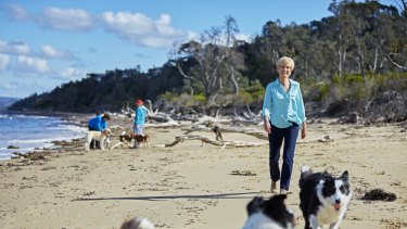 White with her border collies Nellie and Buddy on the beach near her Victorian home.