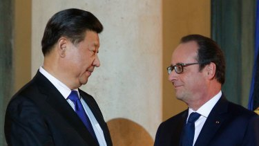 France's President Francois Hollande welcomes Chinese President Xi Jinping prior to a working dinner before the start of the talks.
