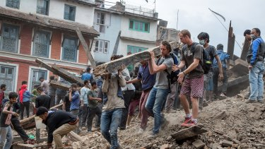 Emergency workers and bystanders clear debris while searching for survivors under a collapsed temple in Basantapur Durbar Square following an earthquake.