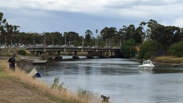 Police divers enter the water where a leg was found near Maribyrnong Road bridge.