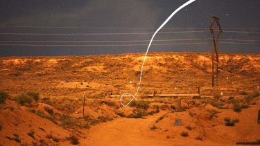 A time exposure, a light-emitting diode, or LED, attached to a self-guided bullet shows a bright path during a nighttime field test.