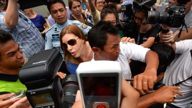 Schapelle's sister Mercedes and husband Wayan fight their way through the media pack to visit Schapelle last Friday.