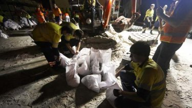 Wave of dread ... volunteers at the council depot in the Brisbane suburb of Stafford prepare sandbags late last night.