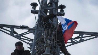 Men hang up a Russian flag on a seized Ukrainian corvette Khmelnitsky in Sevastopol, Crimea.