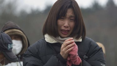 Suffering nation ... a mourner at a mass funeral for victims of the 2011 disaster.