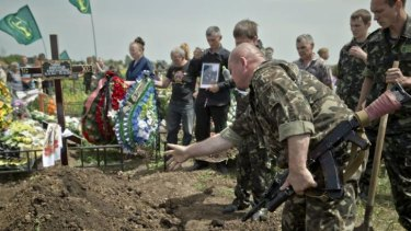 Rising toll ... A pro-Russian rebel throws dirt on the grave of a member of military-patriotic group 'Kaskad' who was killed Monday during clashes with Ukrainian troops, during his funeral in Luhansk, eastern Ukraine.