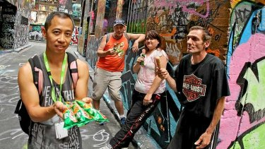 Chito Javier from Youth Projects gives icy-poles to homeless people (from left) Koos, Lisa and Paul.