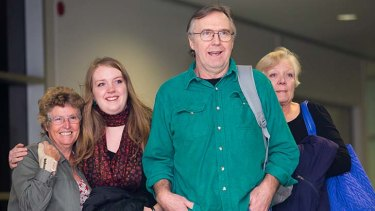 Colin Russell with his wife Christine (right) and daughter Madeleine (second from left) arriving at Hobart Airport.