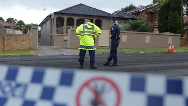 Spike in drive-bys ... police stand guard after several shots were fired at a house on Harris Street in Merrylands today.