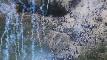 Syrian and Palestinian protesters on the Golan Heights flee from tear gas fired at them by Israeli troops.