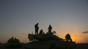 Israeli soldiers stand on top of a tank near the Israeli border with the Gaza Strip on August 2.