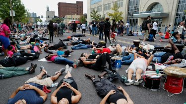 "Demonstrators participate in a ""die-in"" protest outside the St. Louis Police Department headquarters."