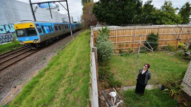Michelle Clarke in the backyard of her Carnegie home which backs on to the rail tracks where the sky rail will be built.