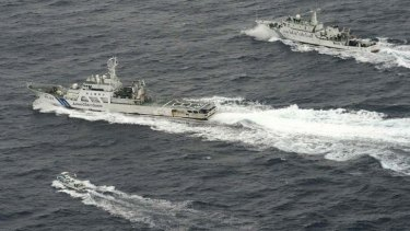 Cat and mouse: a Chinese marine surveillance ship (top) tries to approach one of the Japanese fishing boats (bottom), with a Japan Coast Guard vessel between them.