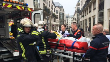 Firefighters carry an injured man on a stretcher from the offices of the French satirical newspaper <i>Charlie Hebdo</i> in Paris after armed gunmen stormed its offices and opened fire.