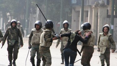 Egyptian army soldiers arrest a female protester during clashes with military police.