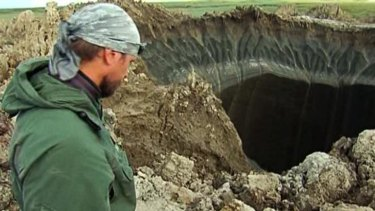Andrei Plekhanov, a researcher at the Scientific Research Center of the Arctic, stands at the entrance to the crater.