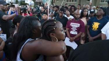Kimberly Neal (braids) is embraced at a gathering in memory of her brother where he was shot and killed in Milwaukee, Wis. , Sunday, Aug. 14, 2016. Milwaukee Police shot and killed 23-year-old Sylville Smith near this spot on Saturday. Police in Milwaukee say a black man whose killing by police touched off arson and rock-throwing was shot by a black officer after turning toward him with a gun in his hand. (Mark Hoffman/Milwaukee Journal-Sentinel via AP)