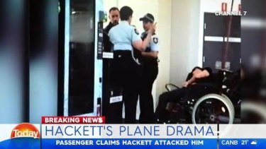This image purports to show Grant Hackett slumped over next to police at Melbourne Airport.
