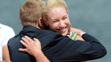Australia's Kim Crow wins bronze in the women's single sculls and receives her medal from John Coates.