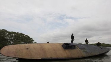 Columbian Navy officers guard a cocaine submarine.