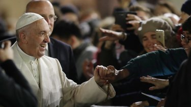 Pope Francis holds hands with faithful after celebrating a new year's eve vespers Mass in St. Peter's Basilica at the Vatican, Saturday, Dec. 31, 2016. (AP Photo/Andrew Medichini)