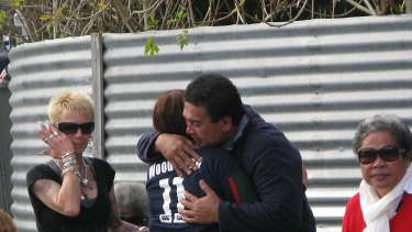 Jeremiah Lale embracing one mourner at the scene of the fire on Thursday.
