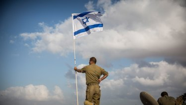 An Israeli soldier stands on top of an armoured personnel carrier near the Israel-Gaza Strip border during Operation Protective Edge in July 2014.