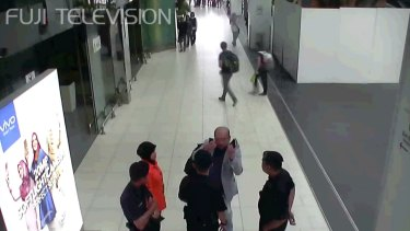Kim Jong-nam, in grey, gestures towards his face while talking to airport security shortly before his death.