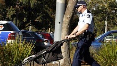 A police officer wheels the toddler's pram.
