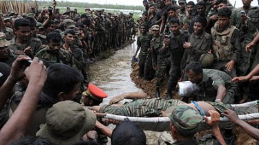 The body of Tamil Tigers leader Velupillai Prabhakaran is carried past Sri Lankan soldiers near Mullaittivu this week.