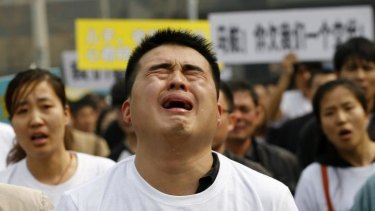 Grief and frustration ... A family member of a passenger on board Malaysia Airlines MH370 cries as he shouts slogans during a protest in front of the Malaysian embassy in Beijing.