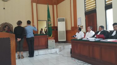 Sara Connor taking an oath before testifying as David Taylor watches on at Denpasar District Court on Monday.