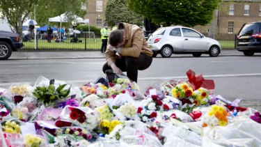 Shock: A man pays his respects as he looks at floral tributes outside Woolwich Barracks in London, where soldier Lee Rigby was brutally killed.