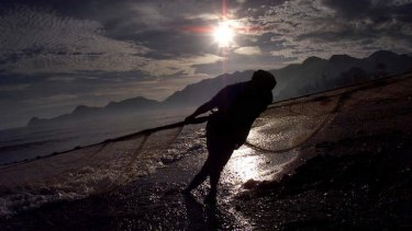 A fisherman brings in nets in Dili, East Timor.