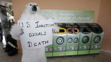 An activist in a bear costume pressures the US at Cancun.