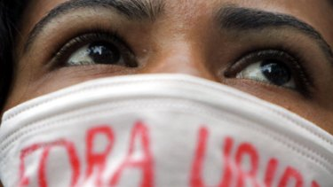 """Continental angst . . . a woman wears a mask that reads """"Get out, Uribe"""" at a protest against the US military presence in Colombia."""