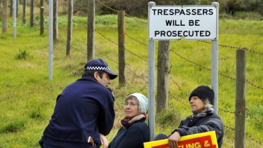 Protesters chain themselves to a sign just inside the desalination plant property at Wonthaggi.