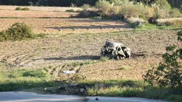 Car of Daphne Caruana Galizia lies next to a road after the explosion.