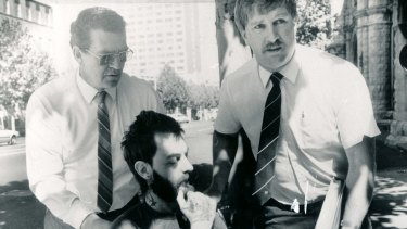 Dennis Bruce Allen, dying of a rare heart disease, is wheeled into court by homicide squad detectives after being charged with murder in August 1984. He died less than five weeks later in hospital.