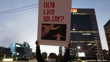 "A protester holds a placard showing South Korean President Park Geun-hye as a puppet with the words ""This is not a country."""