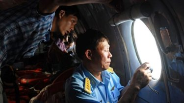 A Vietnamese officer (right) and a reporter looking out the window during search operations over the southern seas off Vietnam.