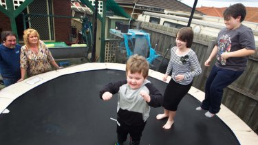 Rowhan, Paige and Roy bounce on the trampoline watched by Paul and Penny Matthews.