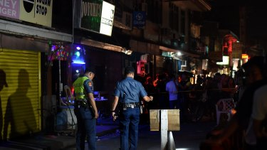 Police at the scene of a double shooting in the Manila suburb of Baclaran, where two masked gunmen shot dead two men aged 21 and 35 who were drinking in a bar.