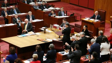Labor senators give Attorney-General George Brandis an unprecedented standing ovation while his Coalition colleagues remain seated following his criticism of Pauline Hanson.