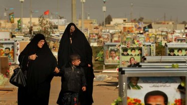 With respect … a family walks past graves at the Shiite militia 'Mahdi cemetery' section at Wadi Al-Salam, among the holiest of burial places for Shiite Muslims.