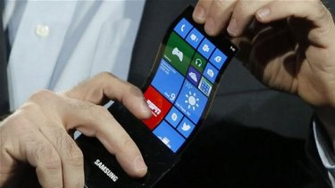 Eric Rudder, chief technical strategy officer of Microsoft, holds a prototype Windows smartphone with a flexible OLED display.