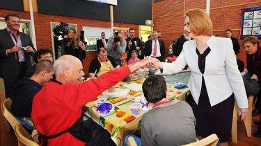 Hands across the table: Julia Gillard with Richard Kindred at a community access program in Tasmania.