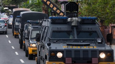 Armed police vehicles complete a practice run to the parole offices in Denpasar, where Corby will sign papers before being deported.